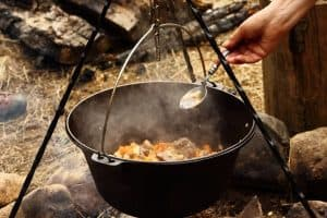 campfire tripod grilling with dutch oven