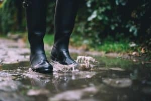 man wearing rubber boots in a puddle in the woods