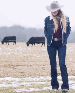 women in western jacket standing in field with cows in the background